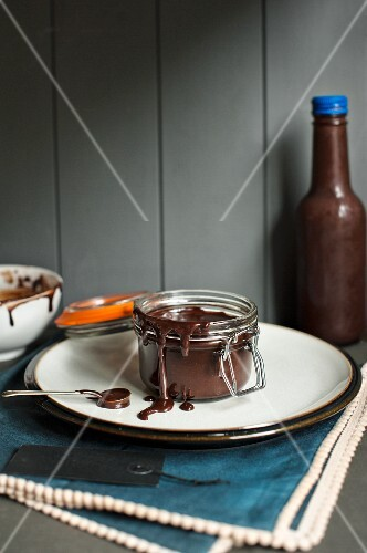An open jar of chocolate fudge sauce on a plate