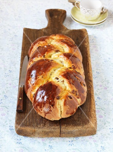A plaited yeast dough loaf with raisins on a chopping board