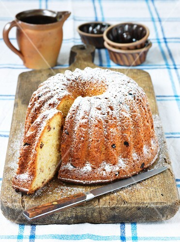 Gugelhupf with raisins and icing sugar, partly sliced