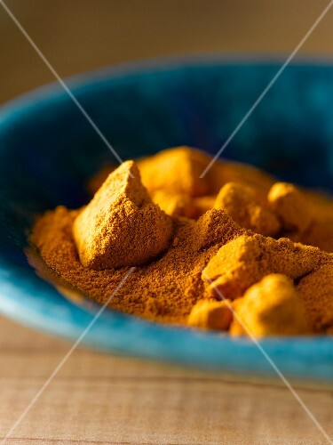 Tumeric powder and chunks in a blue bowl (close-up)