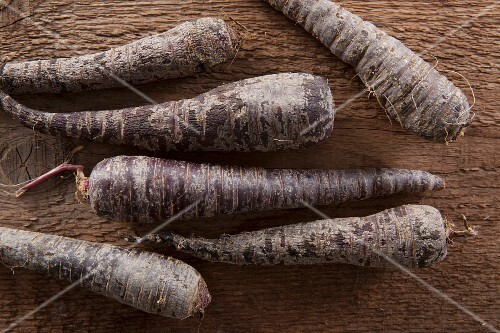 Black carrots on a wooden surface