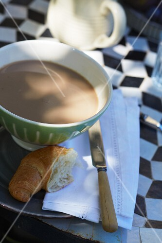 Cafe au lait and croissant on a bistro table with a black and white diamond pattern