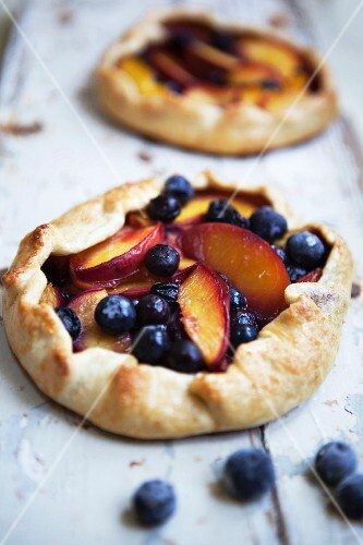 Two blueberry and nectarine galettes on a rustic wooden surface
