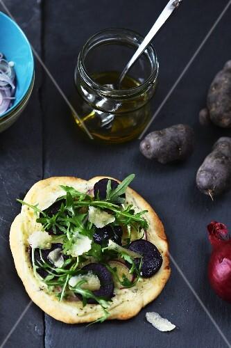 A mini pizza with purple potato slices, rocket and Parmesan