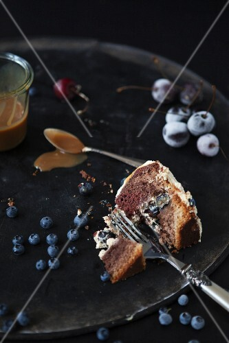 A slice of cake on a plate with a fork, blueberries, cherries and caramel sauce