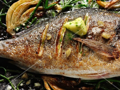Fried sea bass with samphire and herb butter in a pan