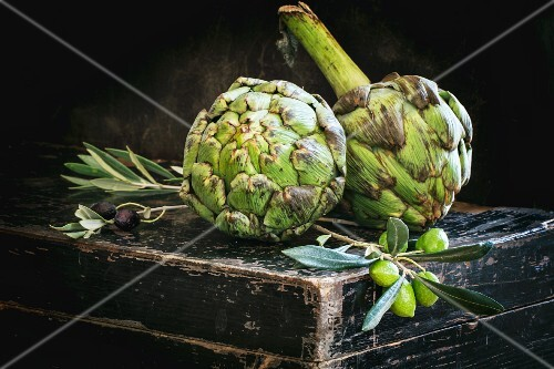 Fresh artichokes and olive sprigs on an old black chest