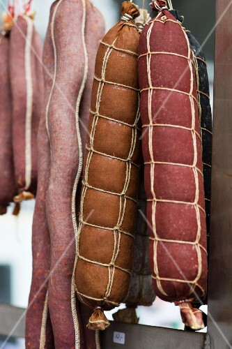 Various types of salami hanging in a butcher's
