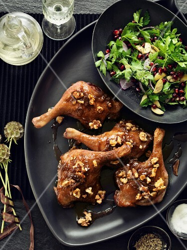 Goose legs with a walnut glaze and a herb salad with pomegranate seeds