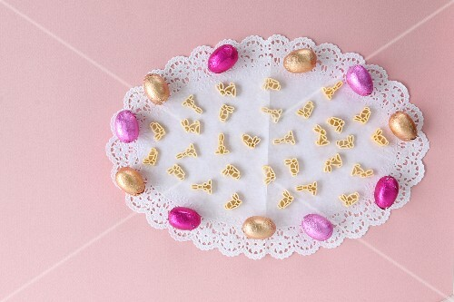 Chocolate Easter eggs and rabbit-shaped pasta on a white doily
