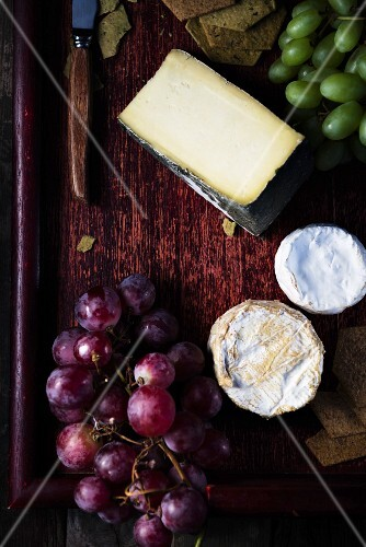 Various types of cheese and grapes on a wooden surface