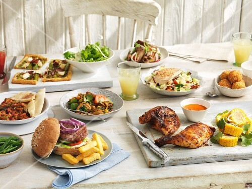 A summer buffet with rocket and rice noodle chicken salad, rice balls, grilled chicken, hamburgers, ratatouille, chicken curry and vegetable tart