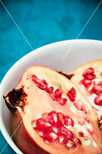 A halved pomegranate in a bowl