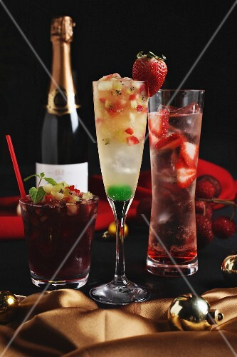 Three different Christmas cocktails with a bottle of champagne in the background