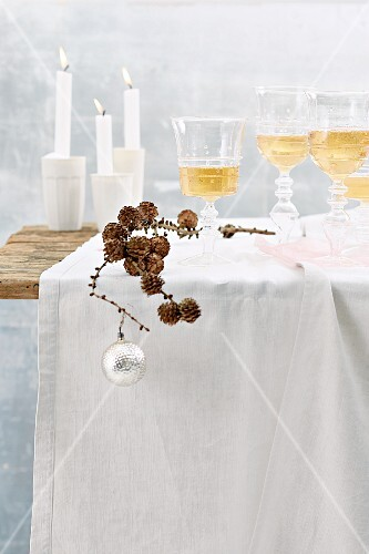 A table laid for Christmas dinner with decorations, wine and candles