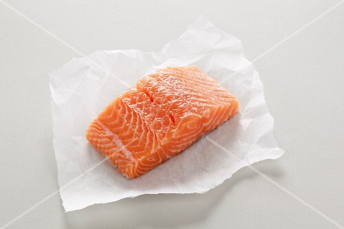 A fresh salmon fillet on a piece of paper