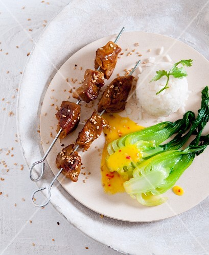 Seitan and sesame seeds skewers with bok choy, orange and chilli sauce and scented rice