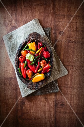 Various fresh chilli peppers in a wooden bowl (seen from above)