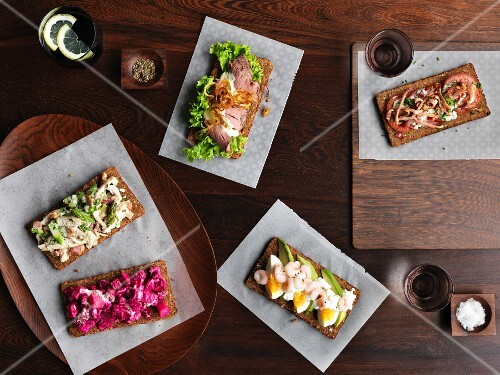 Smörrebröd with various toppings (Denmark) on a wooden table photographed from above
