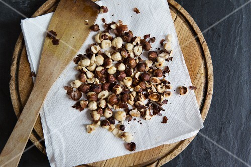 Roasted hazelnuts on a piece of kitchen paper (seen from above)