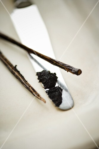 Vanilla seeds on a knife with the scraped-out vanilla pod