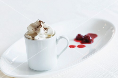 An espresso topped with cream and cocoa