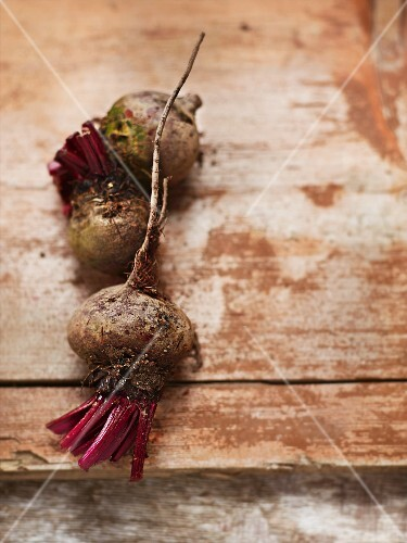 Three organic beetroots on a wooden surface