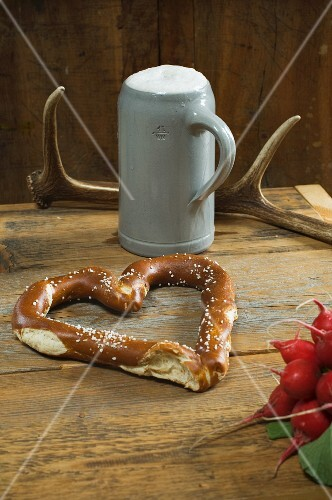 A heart-shaped pretzel with radishes, a mug of beer and antlers on a wooden table