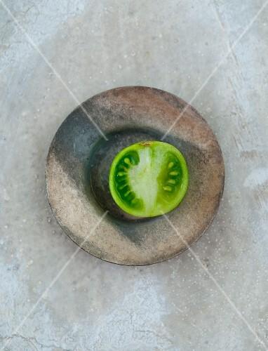 Half a green tomato in a bowl