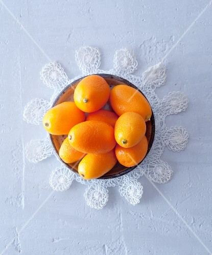 A bowl of kumquats on a lace doily