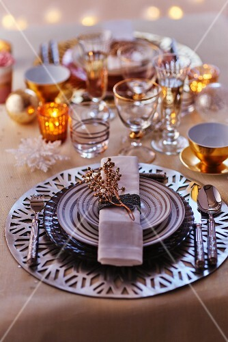 Festive place setting with striped plates, various glasses and tealight holders