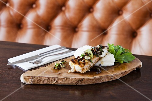 Fish with mashed potatoes and rocket on a wooden board in a restaurant