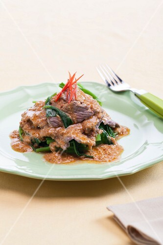 Fried pork with peanut sauce and blanched water spinach (Thailand)