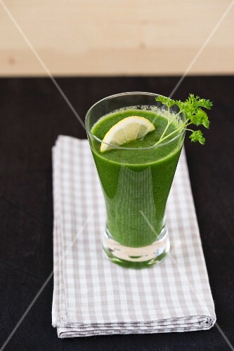 A green smoothie garnished with parsley and lemon