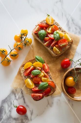 Belegte Brötchen mit bunten Tomaten und Basilikum
