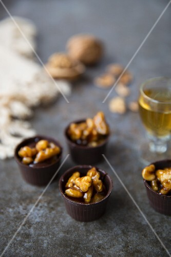 Chocolate cups with caramelized walnuts served with liqueur