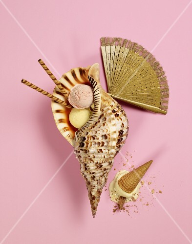 Scoops of ice cream in a shell next to a golden fan and an overturned ice cream cone