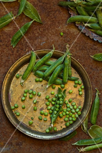 Peas and pea pods on a vintage metal plate