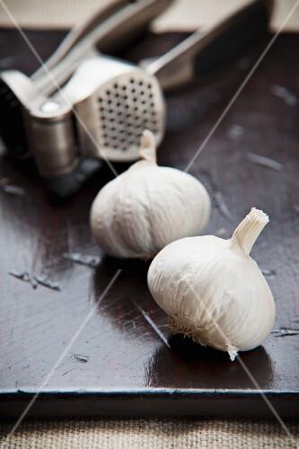 An arrangement of garlic bulbs and a garlic press