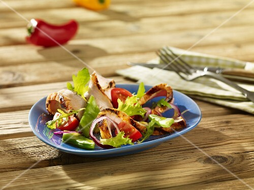Mixed leaf salad with tomatoes and grilled pork