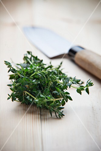 Fresh thyme and a knife on wooden surface