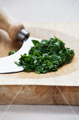 Chopped parsley with a chopping knife on a wooden board