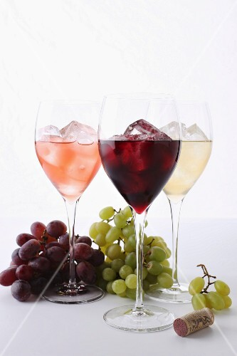 Three different glasses of wine with ice cubes, grapes and a cork