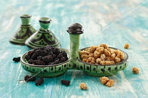Dried mulberries in ceramic dishes