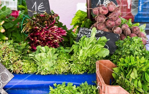 Leafy vegetables, root vegetables and fresh herbs on a vegetable stand