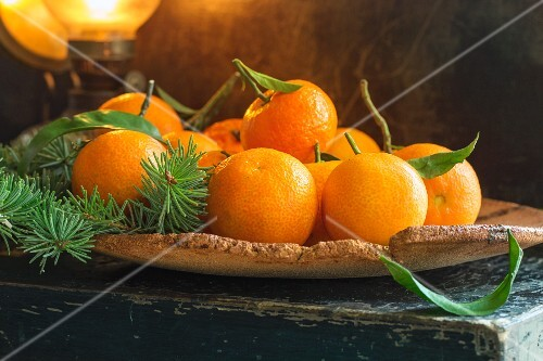 Clementines with leaves on a piece of cork