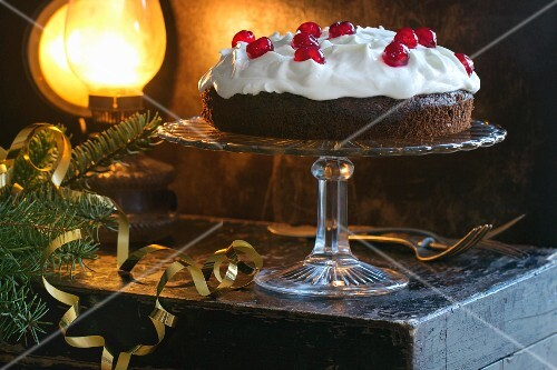 A festive chocolate cake with cream and glace cherries