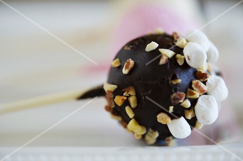 A cake pop topped with chocolate glaze and nuts