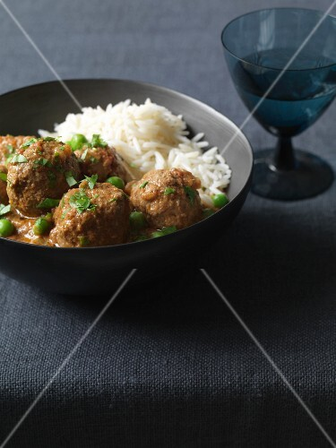 A hearty lamb meatball curry with peas and rice (India)