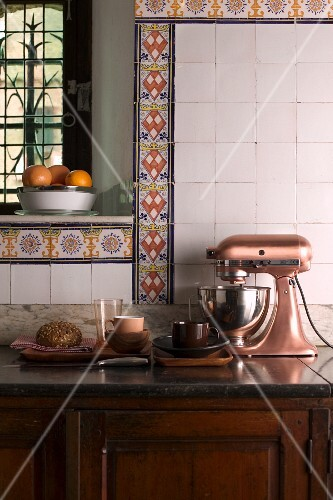 Old, country-house kitchen with vintage-style mixer on rustic base cabinet and decorative borders of colourful patterned tiles on wall